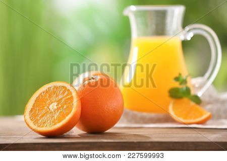 Ripe oranges and pitcher with juice on table