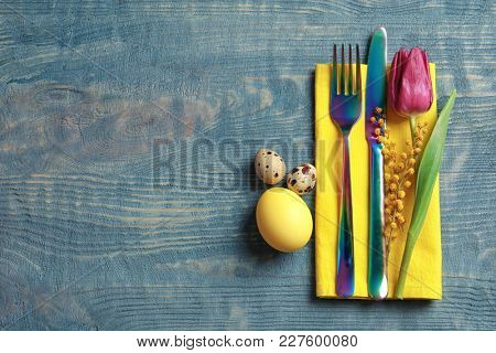 Beautifully decorated cutlery for Easter table setting on wooden background