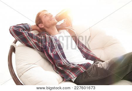 serious guy rests sitting and dreaming in a large comfortable chair.