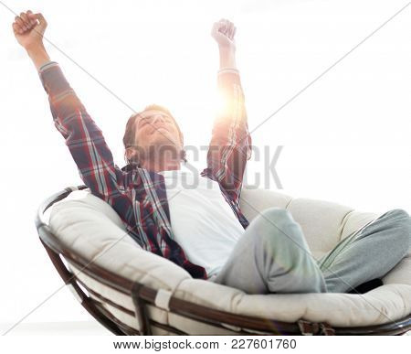 stylish guy stretching in a comfortable chair