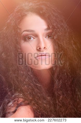 Pretty woman with very long shiny wavy brown hair.