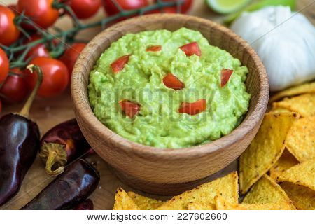 Guacamole In Wooden Bowl With Tortilla Chips And Ingredients