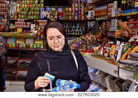 Tehran, Iran - April 29, 2017: A Young Woman Dressed In An Islamic Headscarf Comes Out Of A Grocery