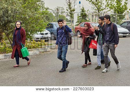 Tehran, Iran - April 29, 2017: Three Young Men And Two Girls In Hijabs Walking Along The Sidewalk.