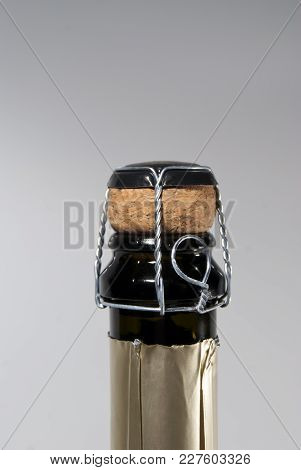 Cork And Muselet Closure Atop A Bottle Of  Sparkling Wine, Unopened, On A Light Background