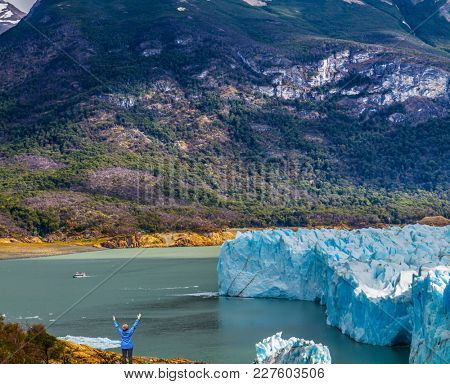 Woman -  tourist enthusiastically raised her hands. Patagonia. Unique lake and glacier Perito Moreno,  in a mountain valley. The concept of  exotic and extreme tourism