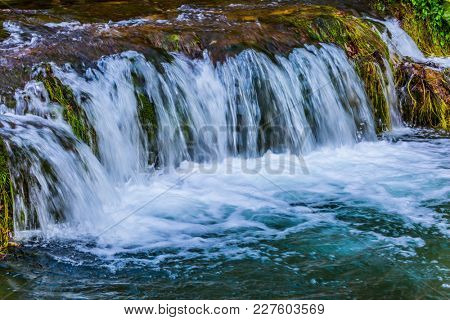 Little beautiful tourist town on the river Koran. Croatia, Slunj. Cascade waterfalls are lit by sunset rays. The concept of ecological, pedestrian and photo tourism