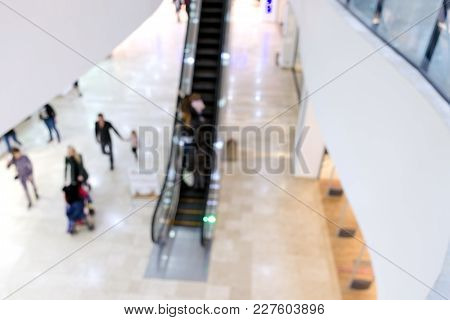 Blurred Photo With Shallow Depth Of Focus Of Interior Shopping Center Hall With An Escalator, People