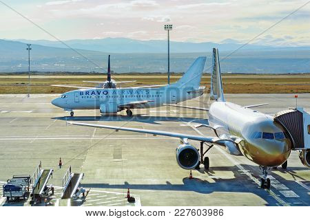 Tbilisi, Georgia, 12/07/2017: Two Airplanes Qatar And Bravo Airways At Airport. To One There Is An J