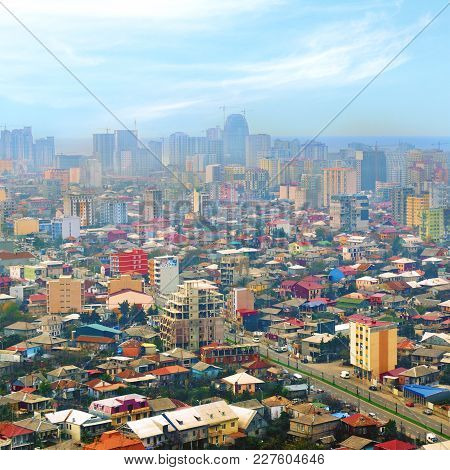 Cityscape With Multi-colored One Story Houses And High Rise Buildings On Horizon. Urban Life. Toned