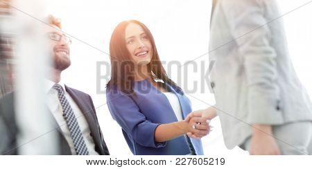 Businesswomen Shaking Hands In Modern Office