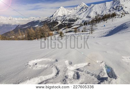 Ski Written On Fresh Powder Snow With European Alps Background