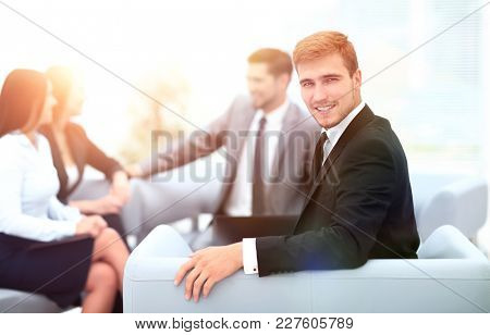 successful business man at the office on the background of busin