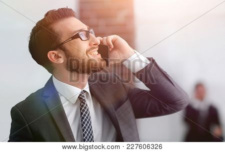 View of a Young attractive business man using smartphone