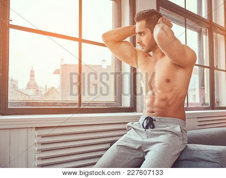 Portrait Of A Shirtless Muscular Man Sits Near The Window.