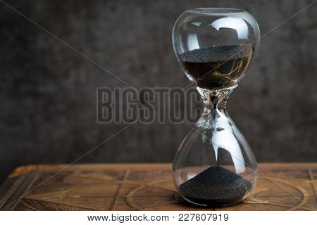Closed Up Of Sandglass Or Hourglass On Vintage Book With Dark Black Loft Cement Background Using As