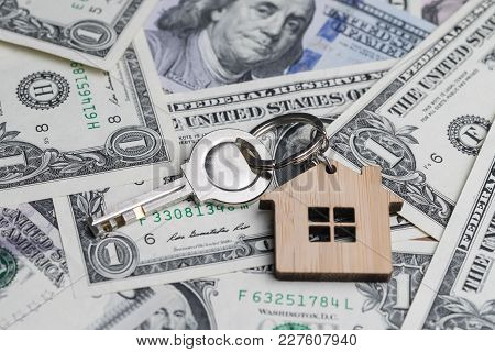 Saving Money For House Or Mortgage Loan Concept, Key With Wooden House Key Chain On Pile Of Us Dallo