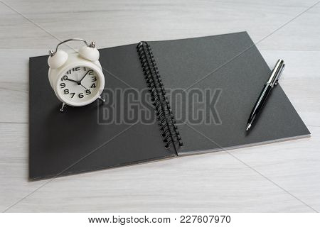 Opening Black Blank Page Paper Book With Pen And White Alarm Clock On Light Grey Wooden Table Backgr