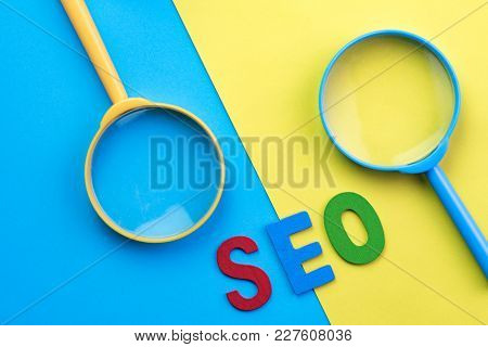 Red, Blue And Green Letters Abbreviation Seo With Blue And Yellow Magnifying Glass On Vivid Opposite
