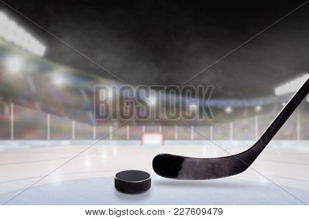 Ice Hockey Stick And Puck In Brightly Lit Outdoor Stadium With Focus On Foreground And Shallow Depth