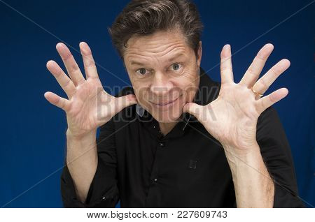 Man Looking Directly At You With Fingers And Hands Wide Open