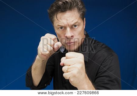 Man Looking Directly At You With His Fists To Fight
