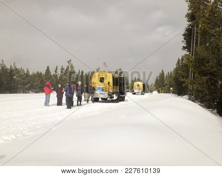 Tourists With Snow Coaches In Yellowstone National Park