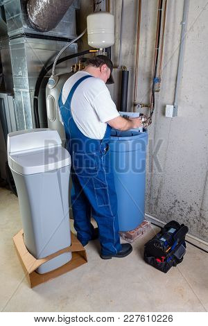 Installer Inputting The Settings On A New Replacement Water Softener That He Has Just Installed In A