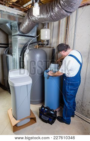 Experienced Home Installer Fixing Issues Encountered On A New Water Softener Tank That He Is Install