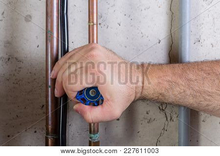 Man Using Strength To Turn A Water Valve On A Pipe Gripping It With His Hand Indoors In A Utility Ro