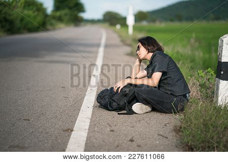 Young Asian Woman Short Hair Sit With Backpack Hitchhiking Along A Road Wait For Help In Country Roa