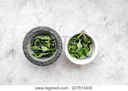 Harvest Medicinal Herbs. Greens In Mortar Bowl On Grey Background Top View.