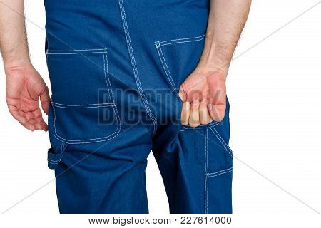 Workman In Denim Dungarees Tugging At The Fabric Over His Backside To Alleviate A Discomfort In A Cl