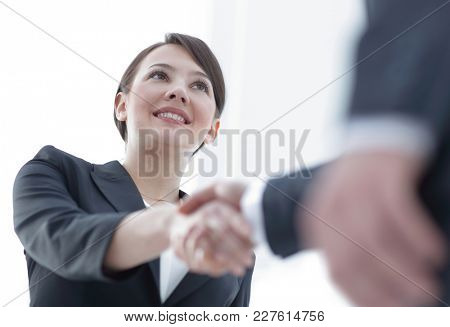 closeup of business woman shaking hands with her business partner.