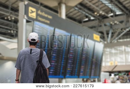 A Man With Backpack Looking On Departure Flight Information Board, For Travel, Go Back Home And Holi