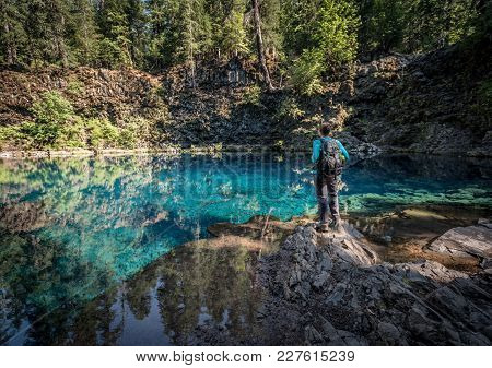 Woman Stands Over Blue Pool In Oregon Wilderness