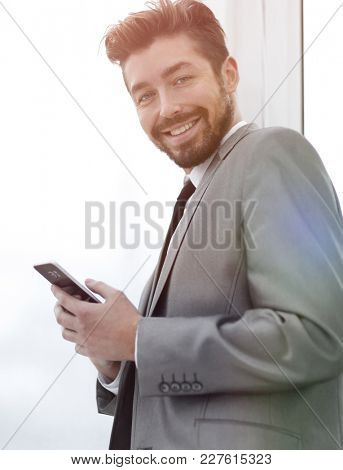Stylish man in suit is reading information on phone