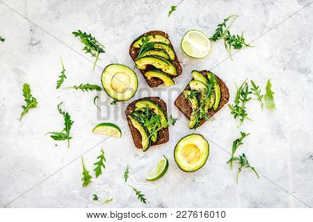 Have A Bite With Healthy Snacks. Avocado Toast On Grey Background Top View.