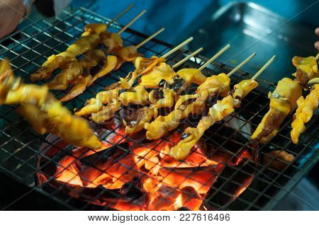 Grilled Squid Hand Cooking On Stove, Thai Cuisine Traditional Street Seafood Stick