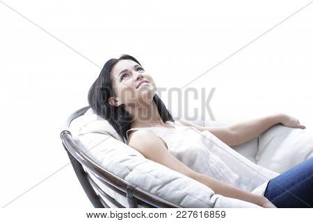 beautiful young woman relaxing in a round cozy soft chair.