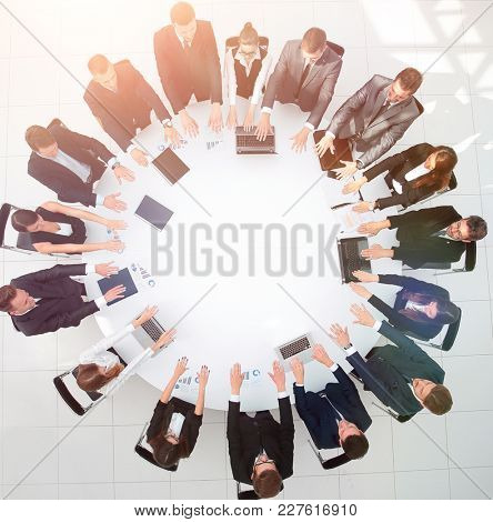 group of business people sitting at the round table, and putting his palms on the table