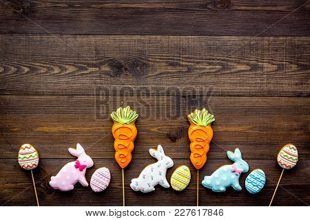 Easter Background. Cookies In Shape Of Easter Bunny And Easter Eggs. Dark Wooden Background Top View