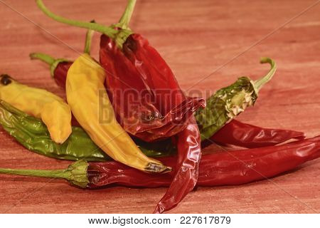 Shrinking And Mould Chili Peppers On Red Wooden Background. Rotten Chili Peppers.