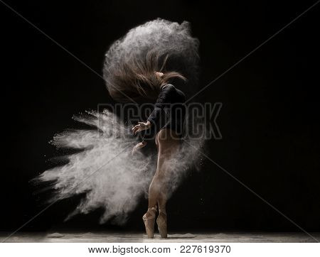 Woman In Undrewear And Pointe Shoes Jumping Gracefully In A White Dust Cloudin Dark Room