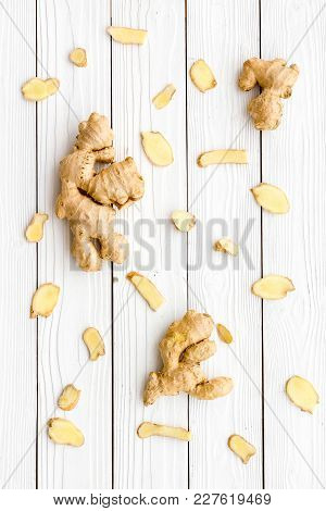 Whole And Sliced Ginger Roots On White Wooden Background Top View.