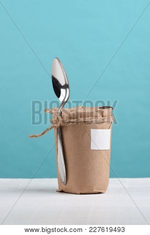 Spoon tied to a jar wrapped in brown paper and tied with twine. On a white wood table and teal background.