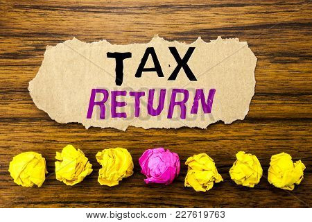 Handwriting Text   Tax Return. Concept For Taxation Refund Written On Sticky Paper Reminder, Wooden