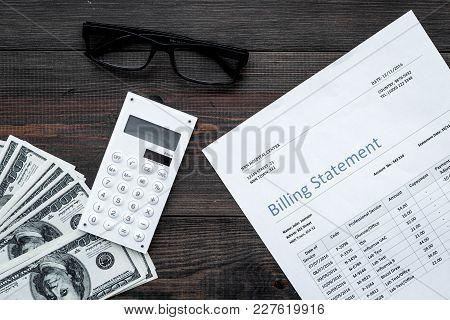 Paying Bills. Billing Statement Near Calculator, Money, Glasses On Dark Wooden Background Top View.