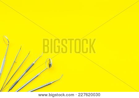 Metal Dentist Tools. Yellow Background Top View.