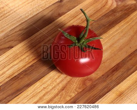 Red Juicy Tomato With A Twig On An Oak Board